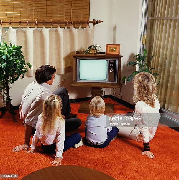 Family on floor watching television