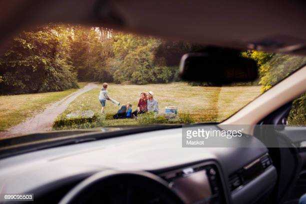 Family on grass at park seen from car windshield