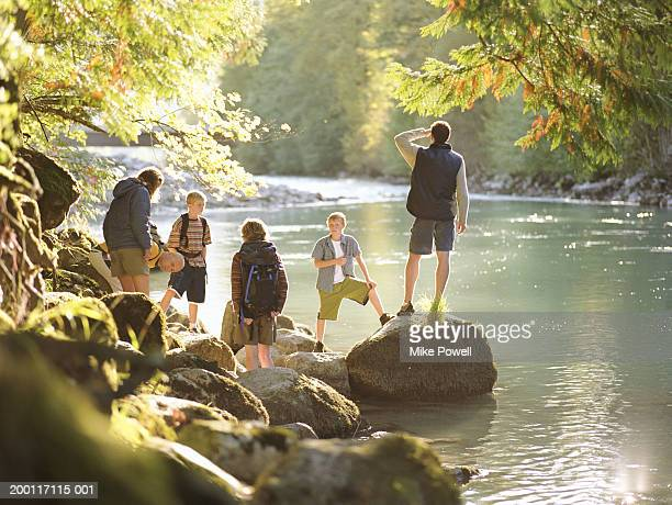 Family on hike, standing on rocks next to river, Boys (8-10)