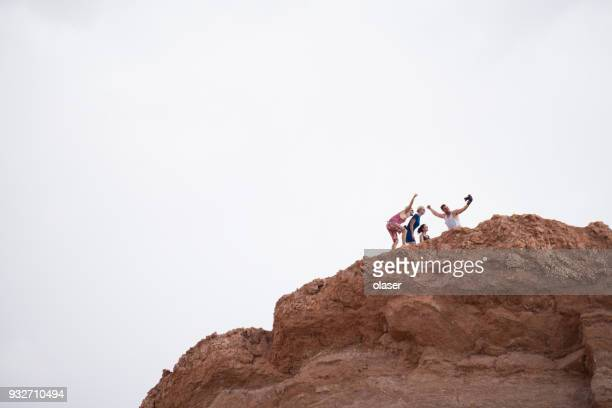 family on mountaintop. taking selfie. moon valley. - antofagasta region stock photos and pictures