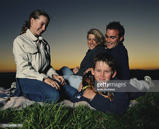 Family on picnic blanket, smiling, ground view