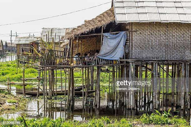 family on porch of bamboo house - merten snijders stockfoto's en -beelden