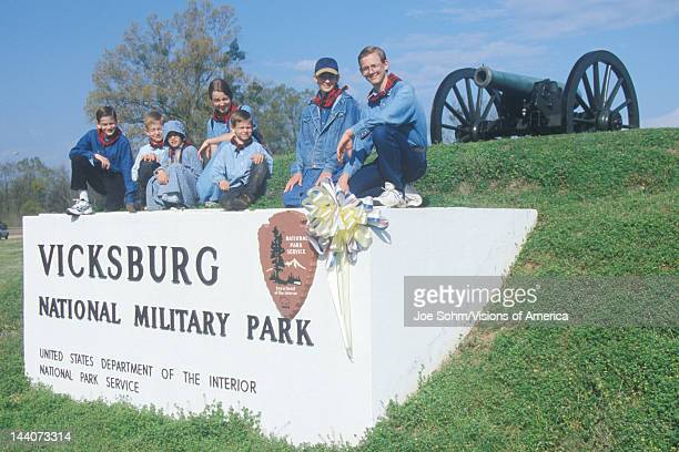 Family on sign on green grass at entrance of Vicksburg National Military Park MS