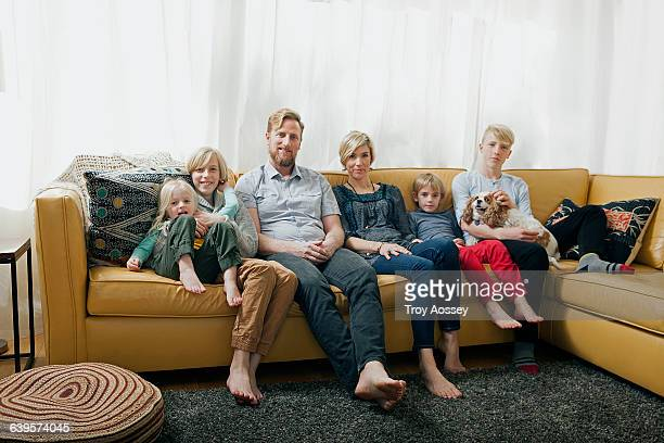 family on sitting on couch - einzelnes tier stock-fotos und bilder