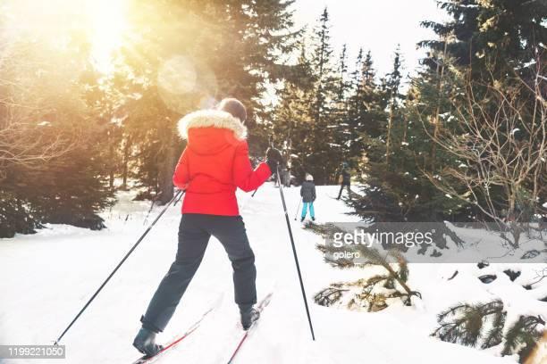 雪のフォレストでスキーハイキングの家族 - クロスカントリースキー ストックフォトと画像