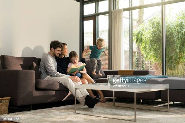 family on sofa at home reading book with boy jumping - four people stock pictures, royalty-free photos & images