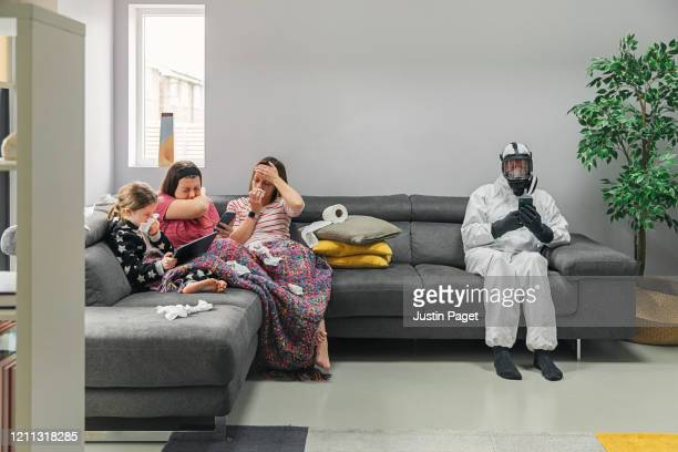 family on sofa. three has the flu. the dad isn't taking any risks! - handkerchief stock pictures, royalty-free photos & images