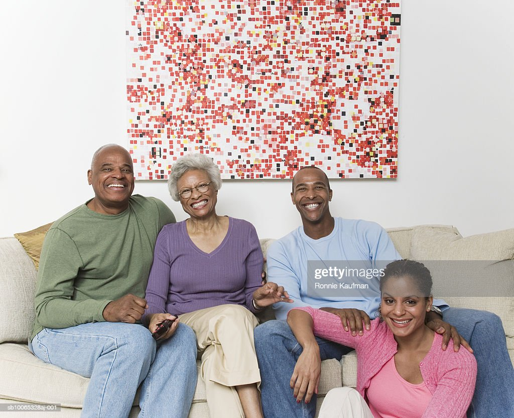 Family on sofa watching television, smiling : Foto stock
