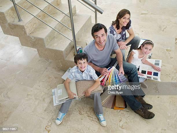 Familie auf Treppe, die auf Farbe und Teppich Proben