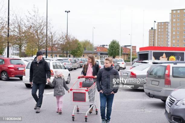 family on store parking - parkplatz stock-fotos und bilder