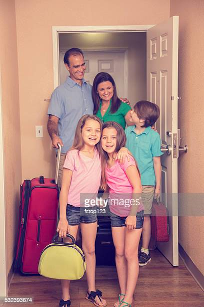 Family on summer vacation enters hotel room. Excited.