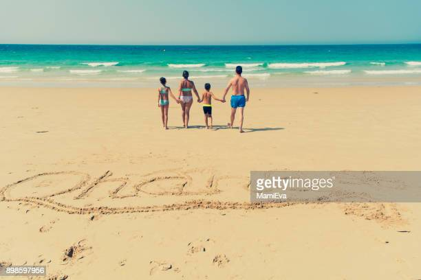Family on the beach and the Word Ohana written in the sand