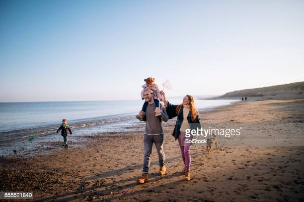 family on the beach during winter - weekend activities stock pictures, royalty-free photos & images