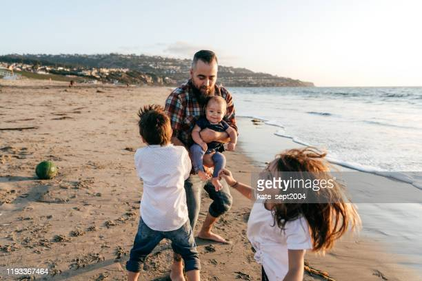 family  on the beach - pacific ocean stock pictures, royalty-free photos & images