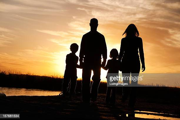 family on the beach - tegenlicht stockfoto's en -beelden