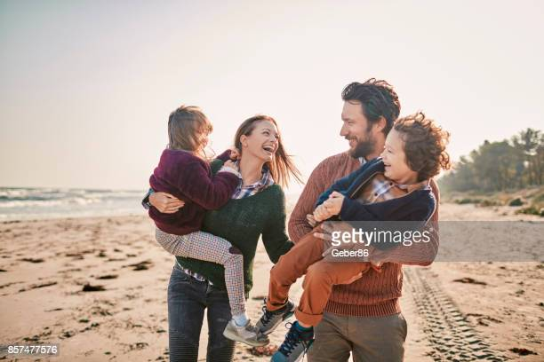 family on the beach - young family stock pictures, royalty-free photos & images