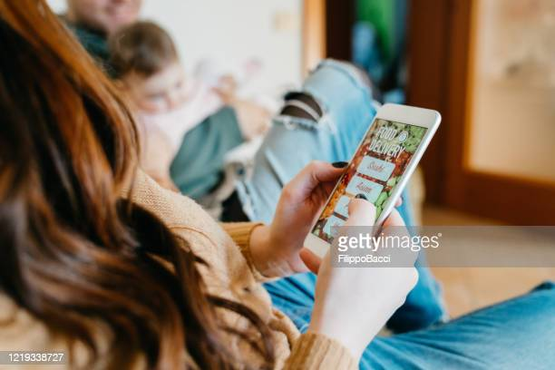 family on the sofa at home - mum is ordering some delivery food for dinner - ordering stock pictures, royalty-free photos & images