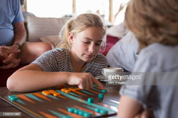 a family on vacation, people playing backgammon at a tented camp in a wildlife reserve. - backgammon stock pictures, royalty-free photos & images