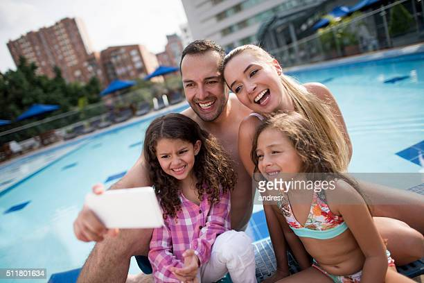 Family on vacation taking a selfie by the swimming pool