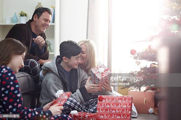 Family opening Christmas gifts at home