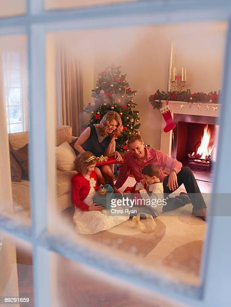 Family opening Christmas gifts in living room