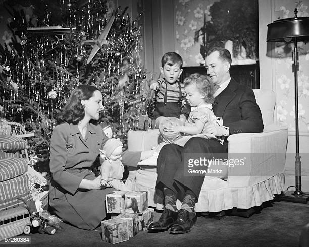Family opening Christmas presents, children (2-3) (4-5), (B&W)