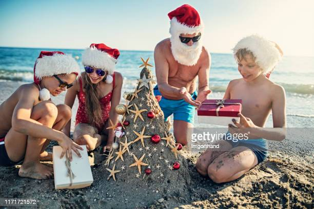Family opening gift under sand Christmas tree.
