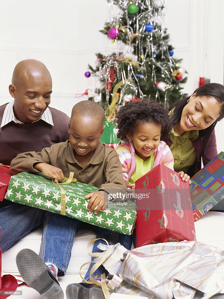 Family Opening Presents Beside A Christmas Tree High-Res ...
