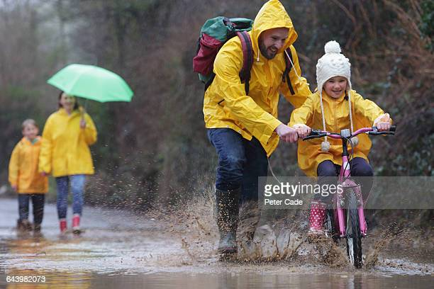 family out in rain and puddles with bike - mother son shower stock photos and pictures