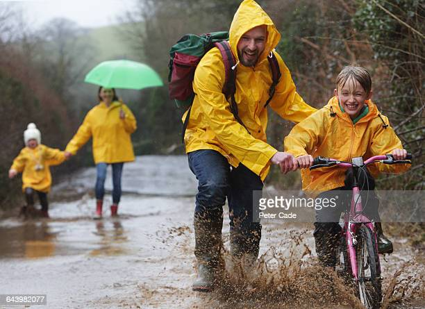 Family out in rain and puddles with bike