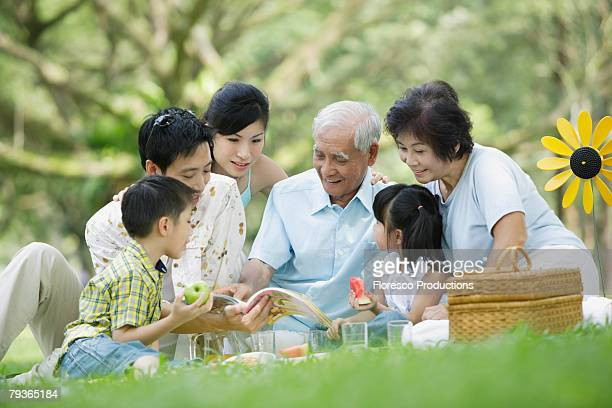 Family outdoors at park having picnic and looking at book