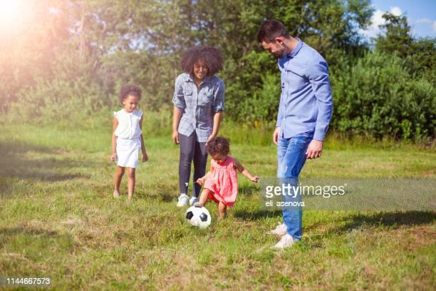 familia al aire libre en verano jugando al fútbol juego en el parque - mama futbol fotografías e imágenes de stock