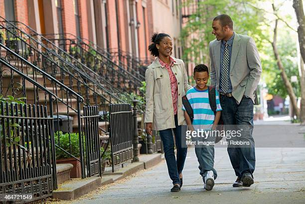 A family outdoors in the city. Two parents and a young boy walking together.
