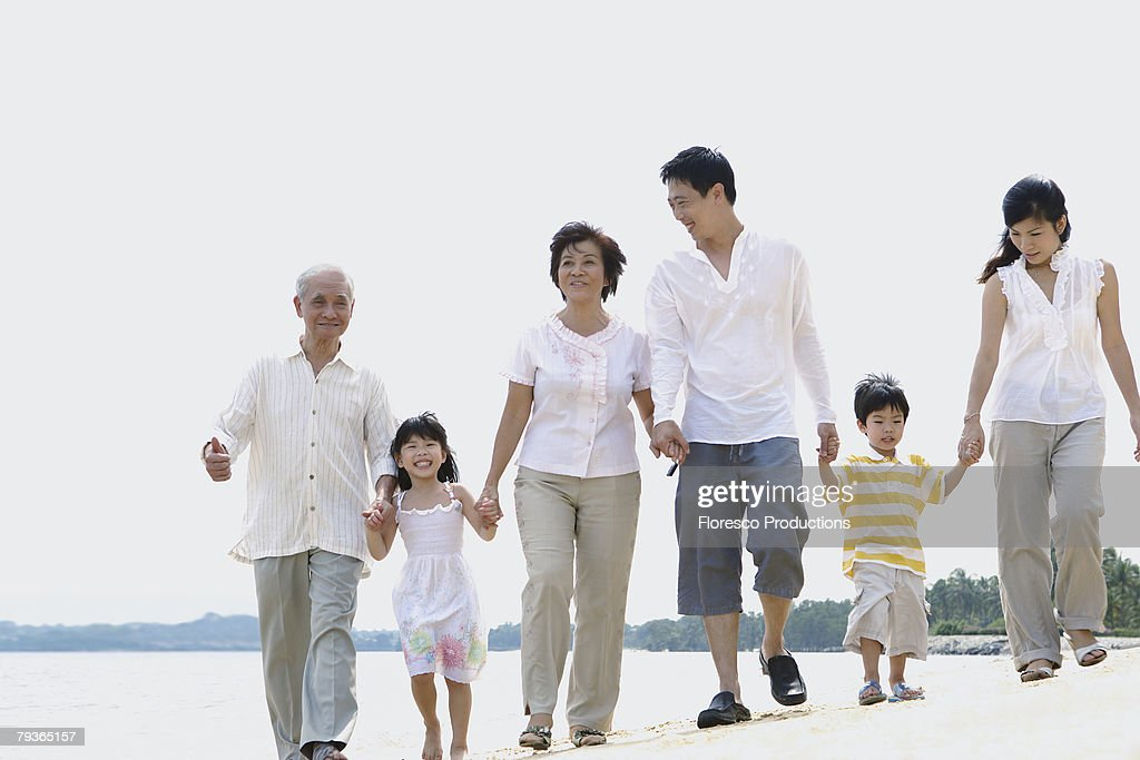 Family outdoors on beach holding hands : Stock Photo