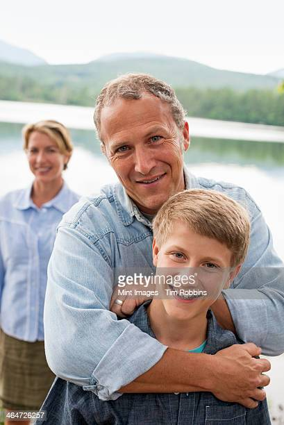 A family outdoors under the trees on a lake shore. Two adults and a young boy.