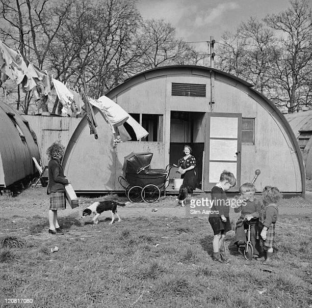 A family outside a prefabricated Nissen hut their temporary home during the postwar housing shortage Southampton circa 1949