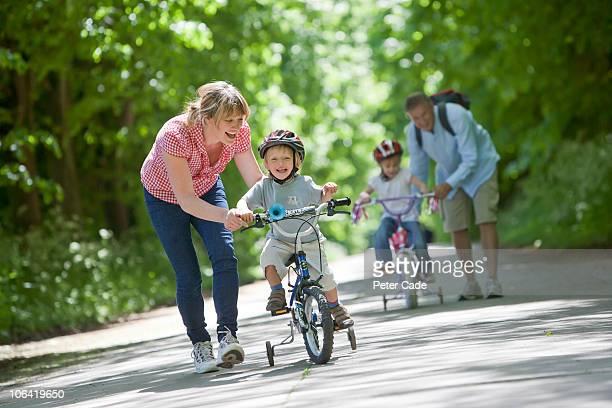 Family outside, children learning to ride bikes