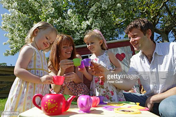 family outside haveing pretent tea party