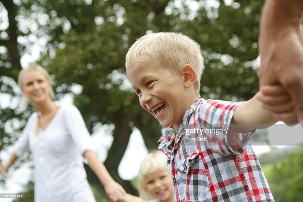 Family outside holding hands : Stock Photo
