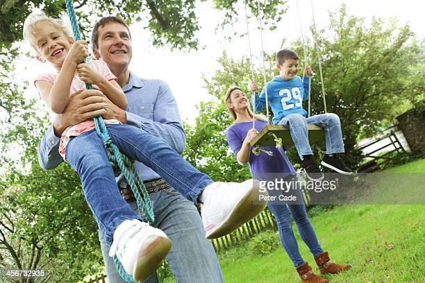 Family outside pushing children on tree swings