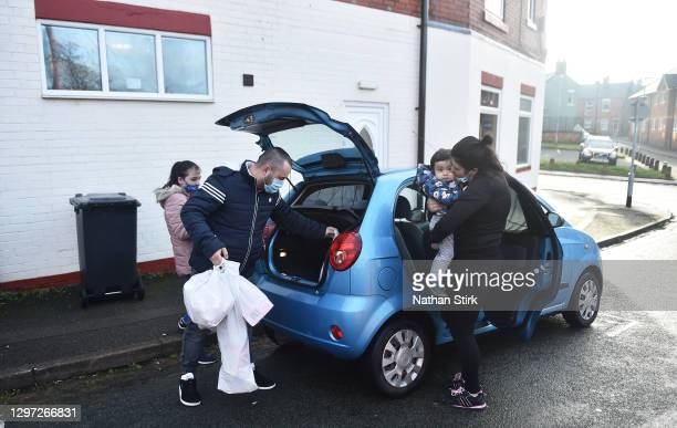 Family pack their car with food from the Tri Service Support Centre food bank, who hosted a community free collection on January 16, 2021 in...