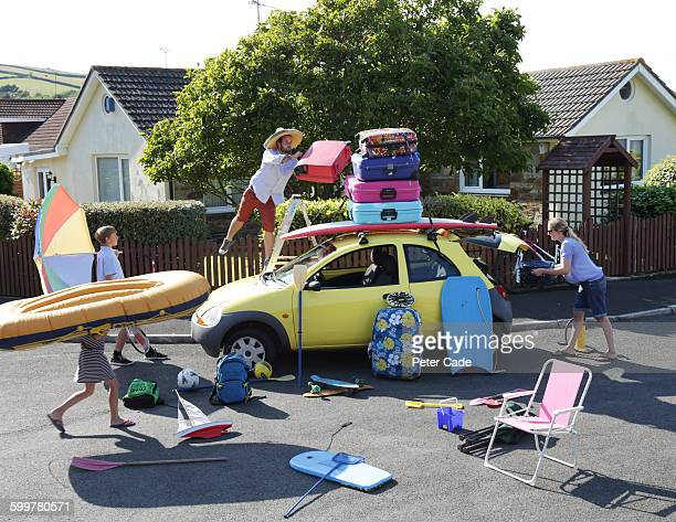 family packing car for holiday - delegating stock photos and pictures