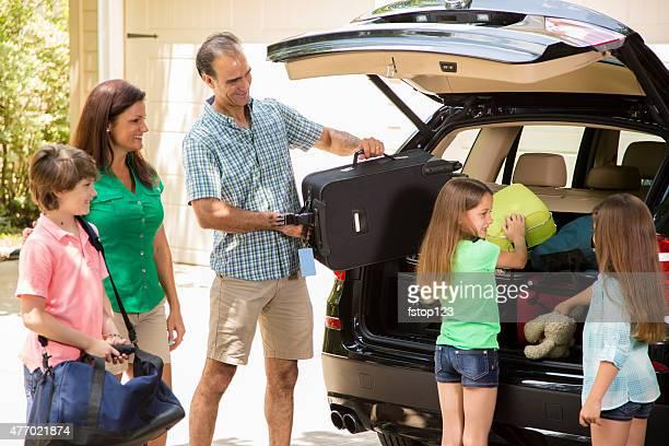 Famille emballage voiture pour aller sur les vacances d'été.   Parents et enfants.