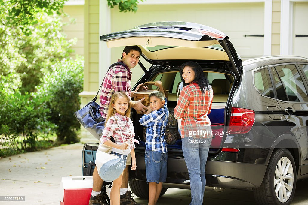 Family packing car to go on vacation. Parents, children. : Stock Photo