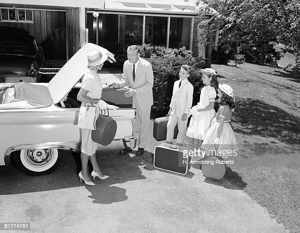 Family packing suitcases in trunk of car parked on driveway, preparing for vacation.