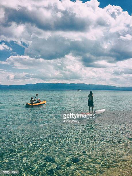 family paddling on lake tahoe during summer - paddling stock pictures, royalty-free photos & images