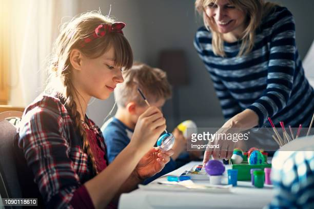 family painting easter eggs - happy easter mom stock pictures, royalty-free photos & images