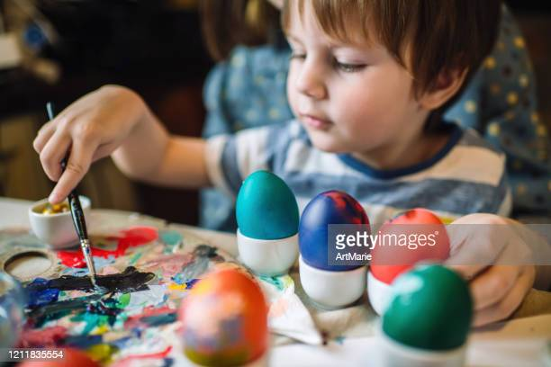 family painting easter eggs - tradition stock pictures, royalty-free photos & images