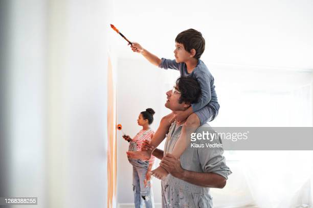 family painting wall during home renovation - painting stock pictures, royalty-free photos & images