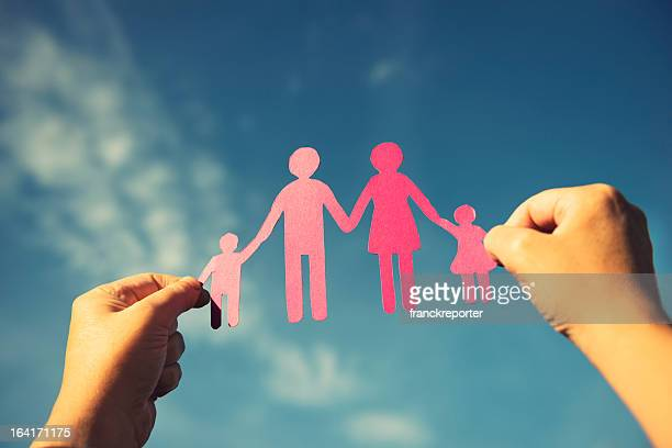 Family paper dolls against the sky